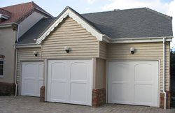 Triple garage in Greenfield, Bedfordshire with Cotswold Moreton up and over doors in white
