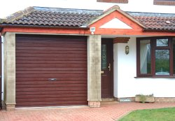 mahogany coated steel timber brown wooden roller shutter garage door installed on a bungaow with brown front door