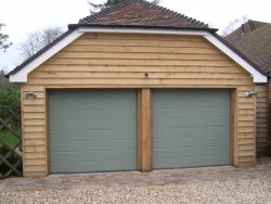 Metallic grey steel sectional garage door installed on timber framework