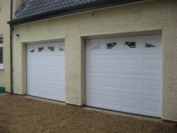 White panelled sectional garage door with sunburst style windows available as an optional extra