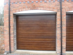 Timber-effect sectional garage door installed on brickwork