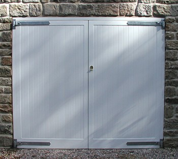 Side hinged white painted garage doors in cedarwood