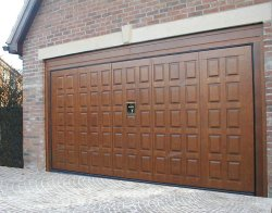 Remote control timber garage door by Silvelox with pedestrian door available in oak, larch or mahogany