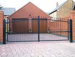 Simple design black painted steel side hinged gates with FAAC automation.