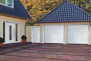 Matching twin steel sectional garage door with matching front entrance and side entrance doors