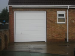 Plain white sectional garage door with a white handle available as an optional extra