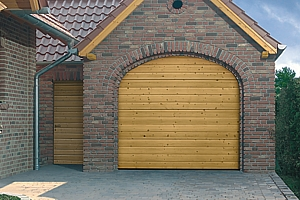 Natural timber sectional garage door installed on brickwork opening with matching side entrance door