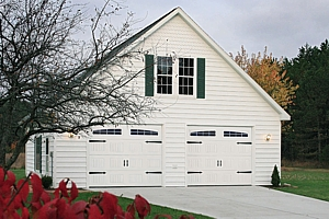Classic style sectional garage doors in white with immitation brackets and windows