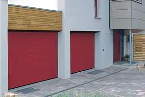 Red sectional garage doors installed on a concrete opening
