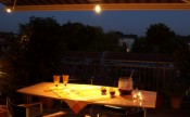 Retractable patio awning at night with adjustable lighting over dining table