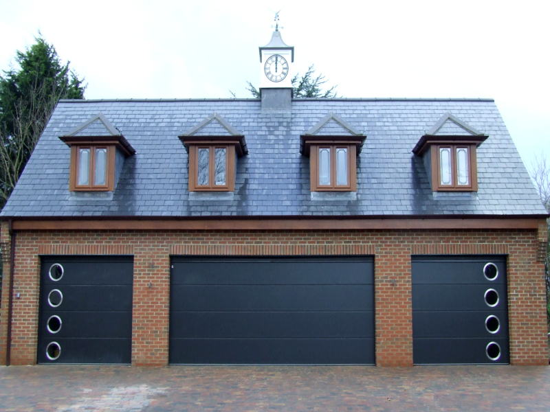 Three anthracite Carteck solid ribbed steel sectional garage doors. Two with porthole windows