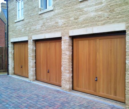 Hormann 2013 Caxton Cedar wood timber doors installed behind triple stone garage
