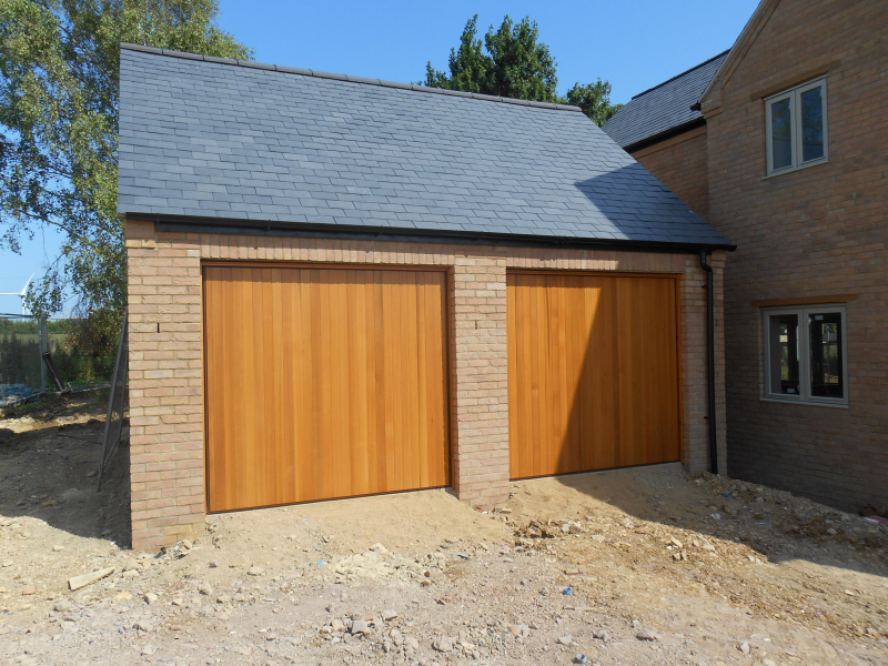 Hormann 2009 Vertical Cedar wood timber doors installed behind twin detached brick garage