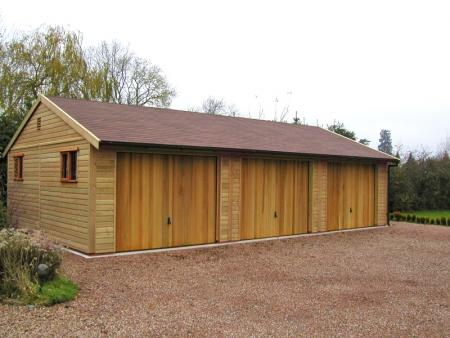 Three Hormann 2009 Vertical Cedar wood timber doors installed behind openings on triple detached timber garage