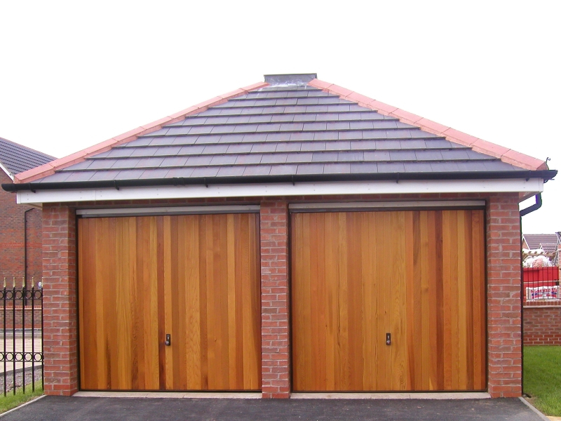 Hormann 2009 Vertical Cedar wood timber doors installed behind openings on twin detached brick garage