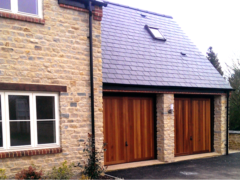 Hormann 2013 Caxton Cedar wood timber doors installed behind twin stone garage