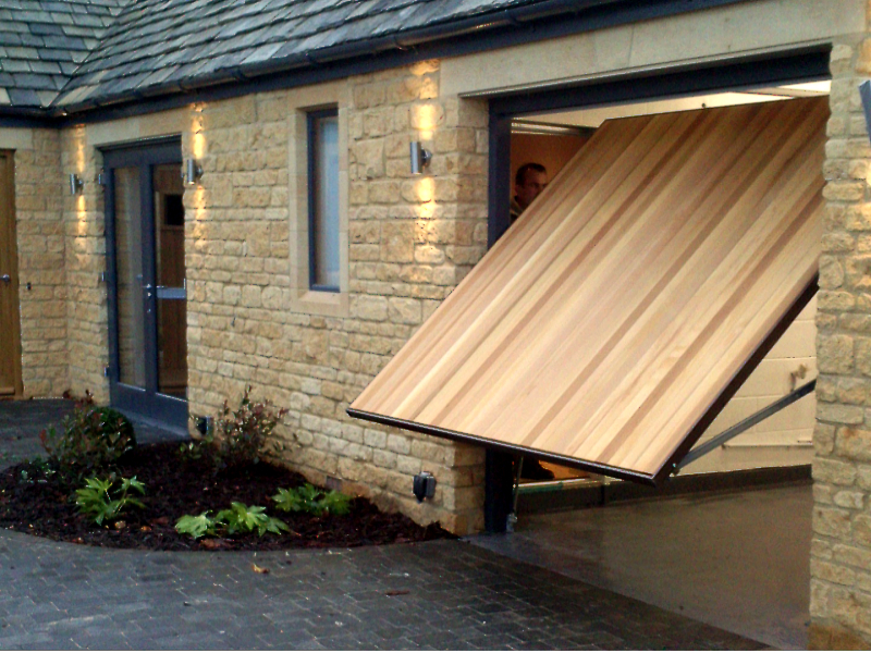 Hormann 2009 Vertical Cedar wood timber door installed behind twin detached stone garage