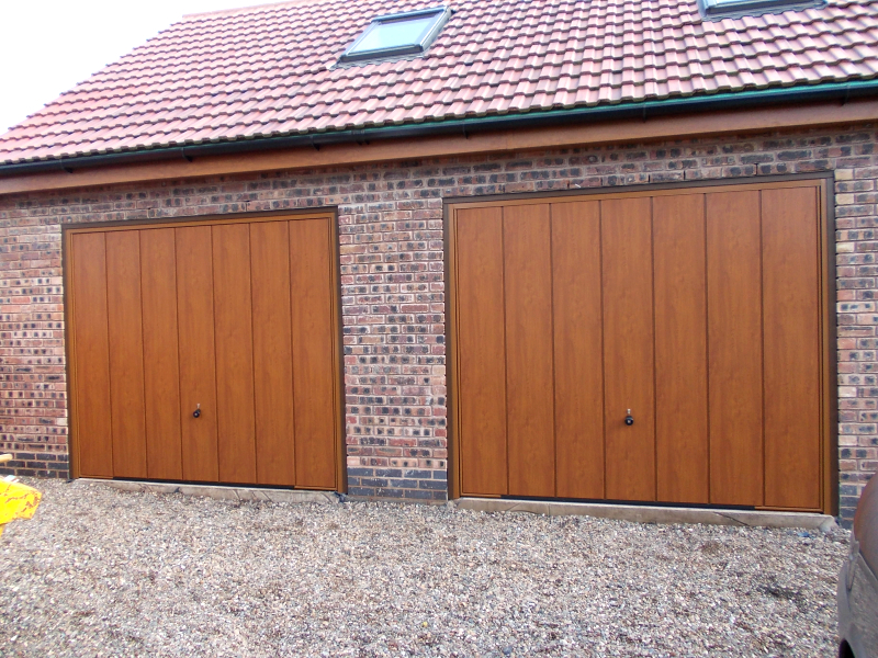 Golden Oak Hormann Vertical Deocgrain steel up and over doors on a twin garage.