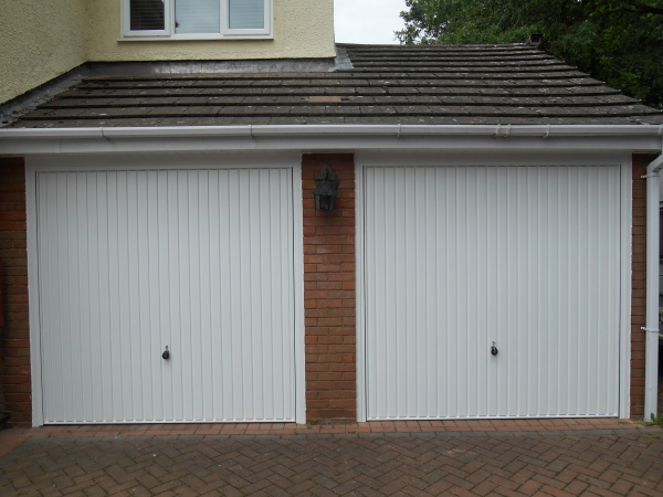 Twin Hormann 2001 vertical ribbed steel up and over doors in white.