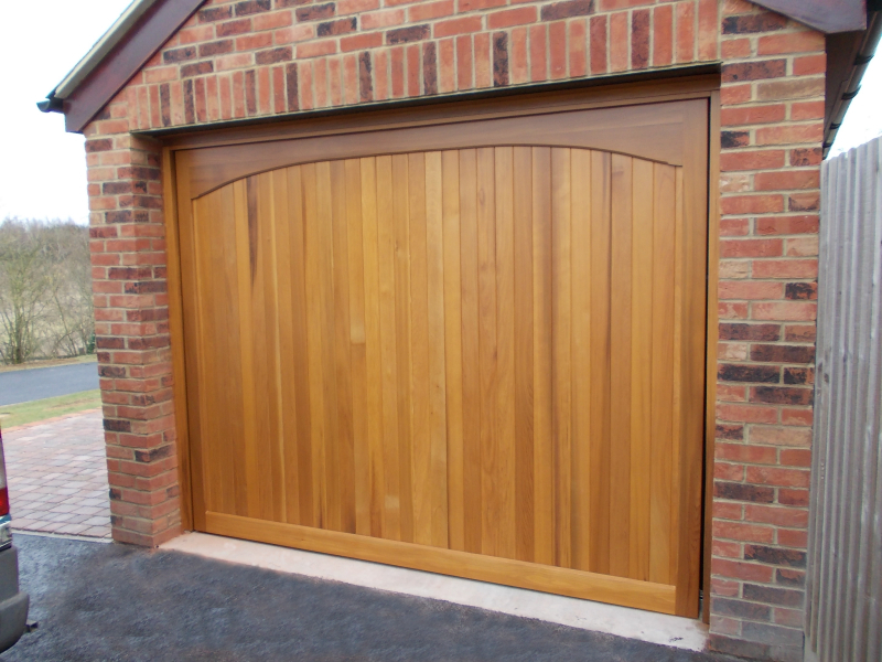 Woodrite Chartridge Wide Board Cedar wood timber door installed behind single detached brick garage