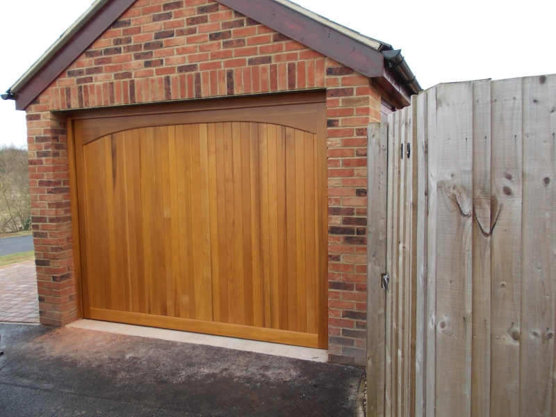 Woodrite Chartridge Cedar wood timber door installed behind single detached brick garage