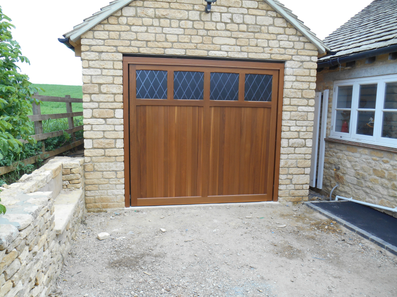 Woodrite Coleshill Cedar wood timber door installed inbetween single stone detached garage