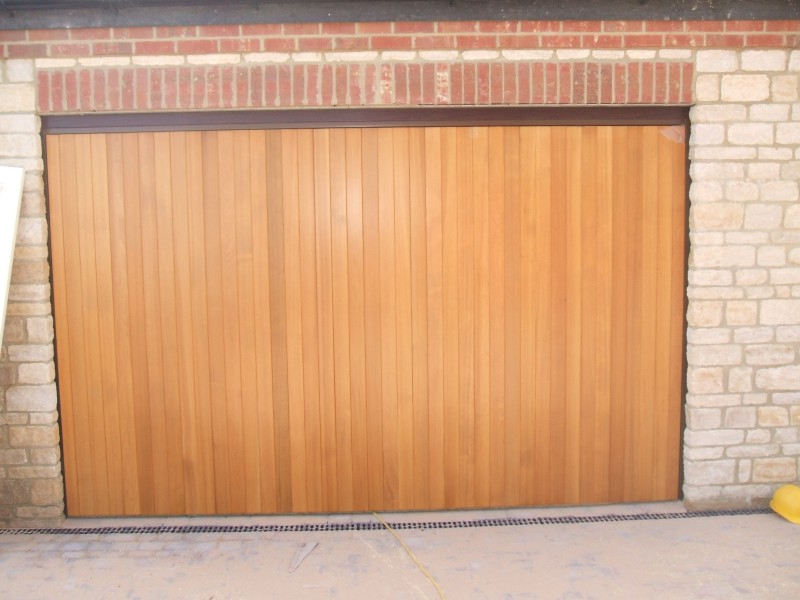Woodrite Tingewick Cedar wood timber door installed behind stone  integral single garage